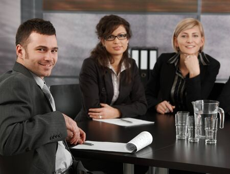 Happy young businessman sitting at meeting table in corporate office, looking at camera, smiling. photo