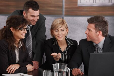 Happy young businesswoman explaining to partners, sitting at meeting table in office, others looking at her, smiling. photo