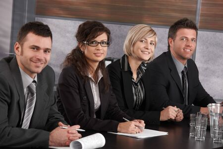 Businesspeople sitting in a row at meeting table in office, looking at camera, smiling. photo