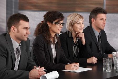conducting: Panel of friendly businesspeople sitting at meeting table conducting job interview.