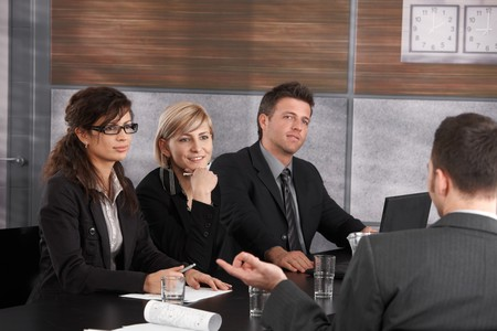 conducting: Panel of friendly businesspeople sitting at meeting table conducting job interview listening to applicant. Stock Photo