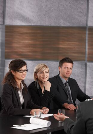 Happy young businesspeople sitting at meeting table, listening and looking at  businessman out of picture. photo
