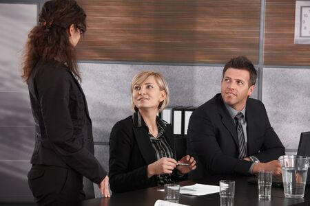 Businesspeople sitting at meeting table, looking up to businesswoman, smiling. photo