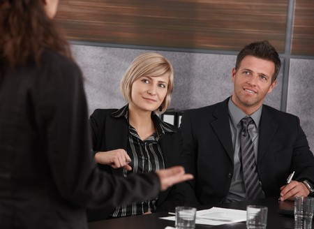 Young businesswoman explaining business problem, others sitting at meeting table, looking at her. Stock Photo - 7520446