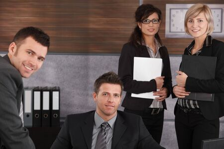 Team of happy businesspeople in office looking at camera, smiling. Businessman sitting colleagues standing around. Stock Photo - 7520445