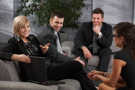discussion group: Satisfied businesspeople sitting on couch in office, businesswoman explaining.