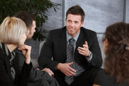 Young businessman sitting at couch in office, explaining something to others, smiling. Stock Photo - 7520463