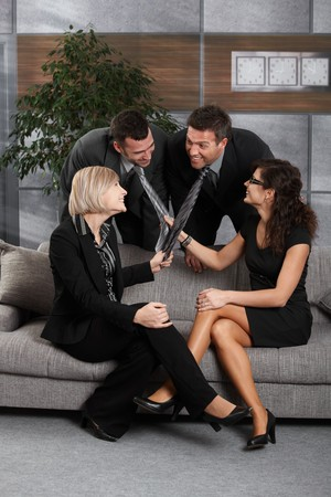 have on: Young businesspeople having fun in office, sitting on couch. Women pulling businessmens tie, laughing. Stock Photo