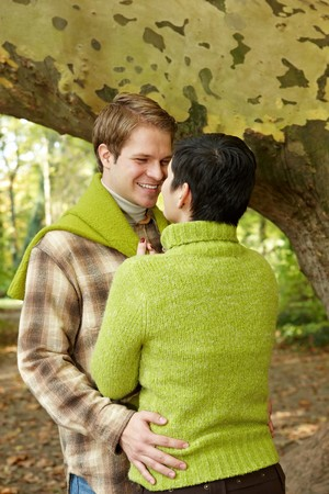 Loving couple embracing in forest, handsome man smiling at girlfriend. photo