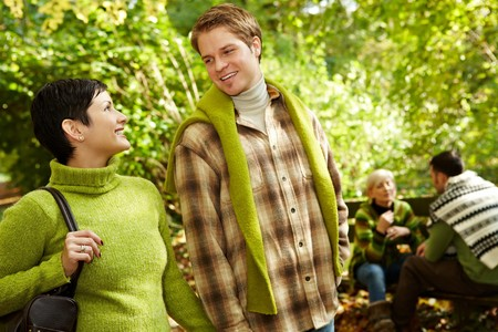 Young couple smiling at each other on forest hiking, with friends in background. photo