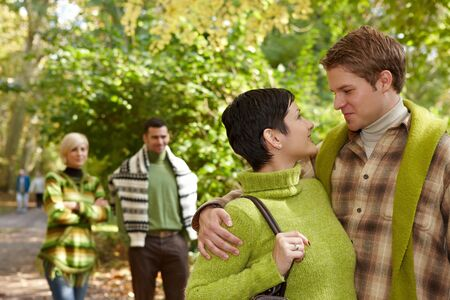 Loving couple embracing in park, friends walking in background. photo