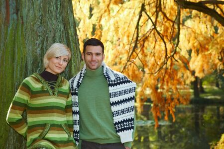 Portrait of young couple in autumn park, standing at tree, smiling at camera. photo