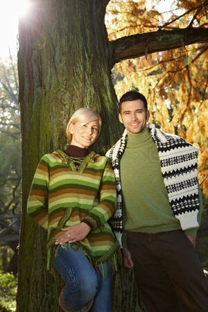 Young couple standing at autumn tree in bright light, smiling at camera. photo