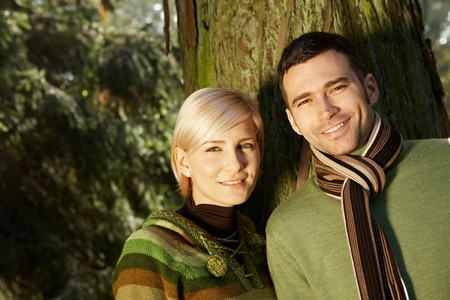 Portrait of young couple standing in park together in sunlight. photo