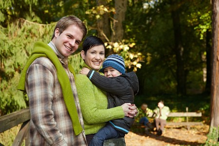 Portrait of happy family of three smiling at camera on autumn hiking. photo