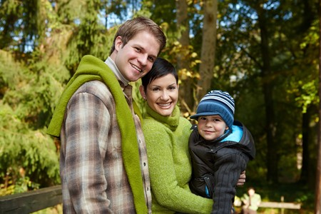 Portrait of happy family of three smiling at camera on sunny day in park. Stock Photo - 7530931
