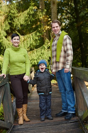 Young happy family of three standing in park on bridge, holding hands, laughing. photo
