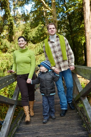 three generations of women: Happy family walking on bridge in autumn forest together, smiling, holding hands.
