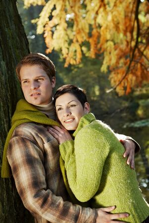 Portrait of young happy couple embracing in bright autumn weather. photo