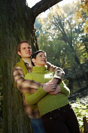 falling in love: Content couple standing at tree in park, embracing, daydreaming in autumn.