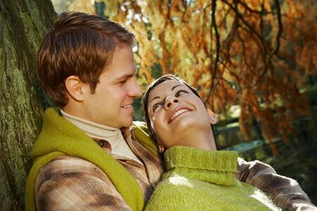 Outdoors portrait of couple in love, embracing at autumn lake in park. photo