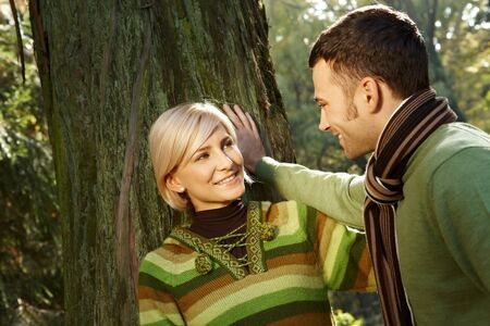 Loving couple smiling at each other standing at tree in park. photo