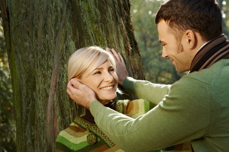 Portrait of happy couple in park, man caressing smiling womans face. photo