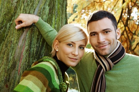 Closeup outdoors portrait of young couple smiling at camera at tree trunk. photo