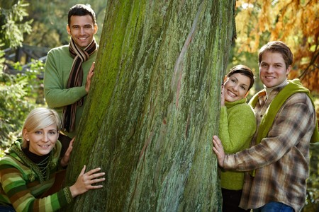 big shirt: Portrait of four friends standing around huge tree in forest, smiling, looking at camera. Stock Photo