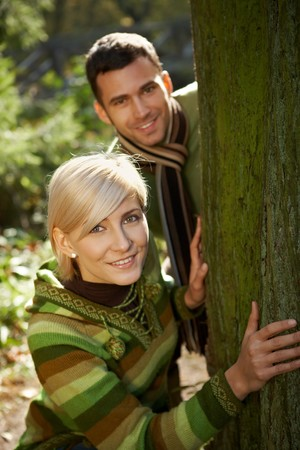 Portrait of young couple having fun in autumn park, smiling at camera. photo