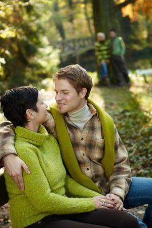 Happy couple sitting embracing on park bench, smiling, friends standing at tree in background. photo