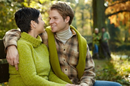 Loving couple embracing on park bench, smiling, friends standing in sunny background. photo