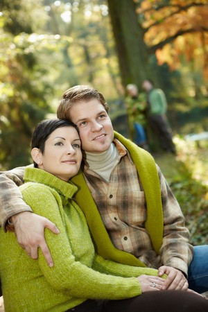 Portrait of content couple sitting in sunny autumn park, smiling, friends in background. photo
