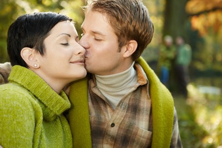 falling in love: Happy couple sitting outdoors, man kissing smiling woman on cheek. Stock Photo