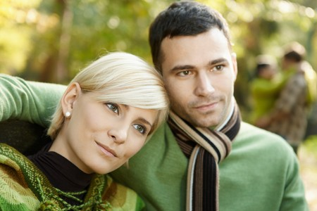 Closeup portrait of young couple embracing in autumn park. photo