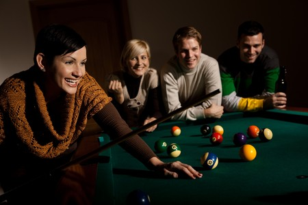 Woman laughing holding cue at snooker table, friends in background. Stock Photo - 7530897