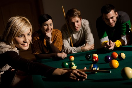 snooker cue: Smiling woman aiming at white ball with cue leaning on snooker table, friends watching.