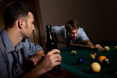 Young man playing snooker, concentrating with cue in hand, friend watching holding beer. photo
