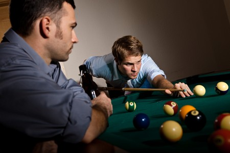 Young man focusing on playing snooker, concentrating on white ball friend watching at table. photo