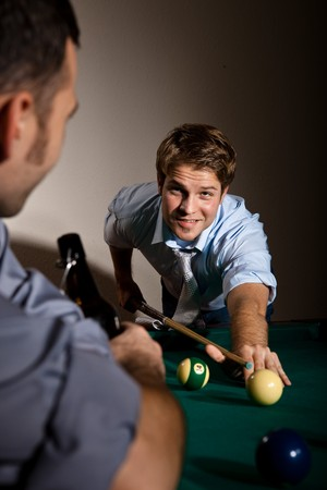 Friends playing snooker at bar, young man looking up smiling, aiming at white ball with cue. photo