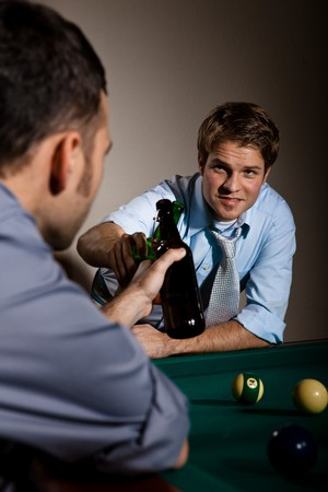 Friends clinking beer bottles at snooker table while playing game. photo