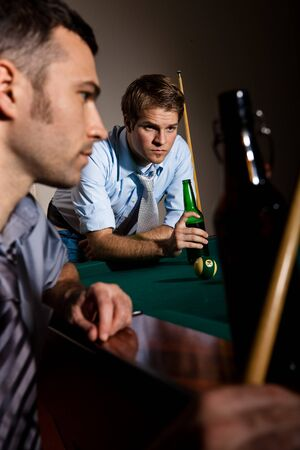 Two men concentrating on playing snooker, drinking beer at game. photo