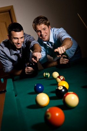 Two young men discussing snooker game, having beer, pointing at balls on table, smiling. photo