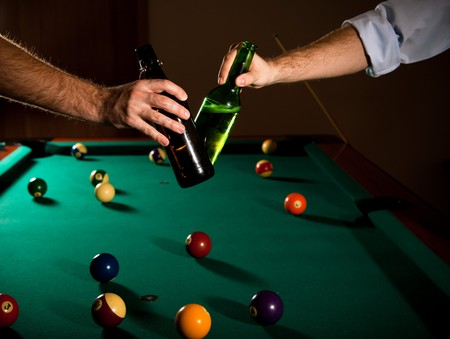 horizontal bar: Men clinking beer bottles at snooker table, while playing game.