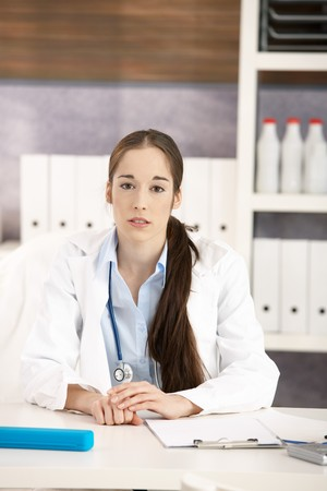 Portrait of female medical doctor sitting at desk in doctors office looking at camera. Copyspace above. Stock Photo - 7530982