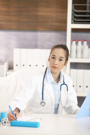 Portrait of young female doctor working in office, sitting at desk doing paperwork, looking at camera, smiling.  photo