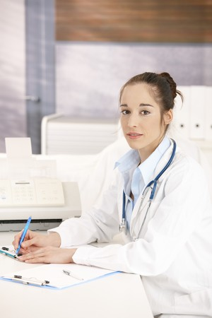 Young female doctor working at desk in doctors room writing, looking at camera smiling. photo