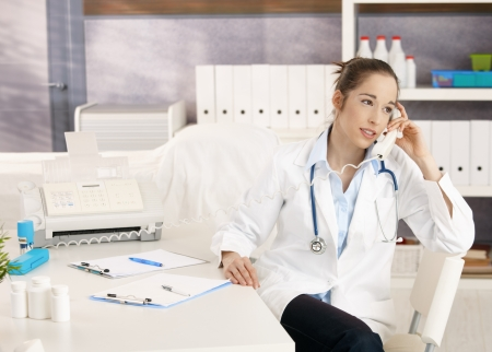 Young female doctor sitting at desk in doctors room calling, looking away, smiling. photo