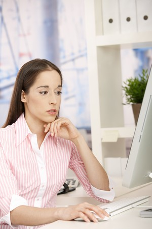 Young assistant girl sitting at desk in office concentrating on computer work.  Stock Photo - 7530992