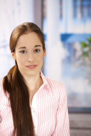Portrait of smiling girl with long hair in ponytail, looking at camera. Stock Photo